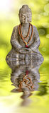 Stone Buddha statue and water reflection Royalty Free Stock Photography