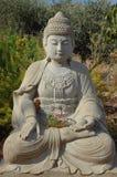 Stone Buddha Staue In Garden. Stone Buddha with an offering of flowers in garden stock photos