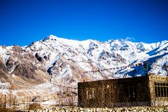 Stone Building at the Base of Snow-covered Mountain Range Under Clear Bright Blue Sky stock photo