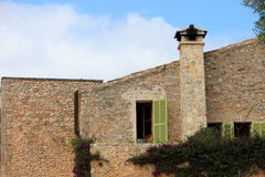 Stone building with chimney. Exterior facade of a stone building with a chimney and windows with green shutters Stock Image