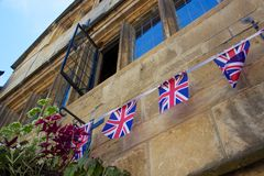 Stone building in England with UK flag bunting. In England in late summer, a golden-stone building is decorated with bunting in the shape of the United Kingdom Stock Photos