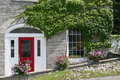 Stone building with red door. A beautiful grey stone building with paned windows, growing ivy Royalty Free Stock Image