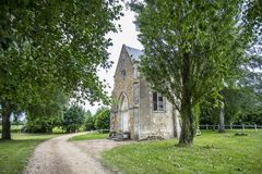 A Stone Building among trees in France. AN old stone building stands among trees by a dirt road near Le Mans, June 2015,  black and white, monochrome Royalty Free Stock Photos