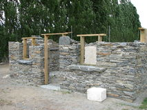 Stone building under construction. A replica of a gold miner's cottage with stone walls, being constructed by a school teaching stonemasonery stock photos