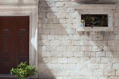 Flower decorated door and window on stone built facade. Stone built house facade with flower decorated door and window. Monumental stonework. Åibenik, Croatia royalty free stock photo