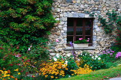 Stone-built house and flowers stock photos