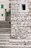 Rustic, white, stone built houses and stairways of old mediterranean town. Stone built houses with small windows and stone slabs stairs of historic Croatian town stock photos
