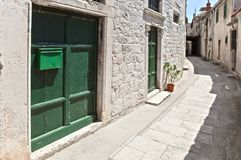 Narrow street in old mediterranean town with green doors on white, stone built facade. Stone built, narrow street curving through old, attached houses of Š Stock Image