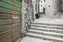 Stone built narrow streets and stairways of Åibenik. Weathered, wooden, green door and white stone of stairways, narrow streets and house facades of historic stock photo