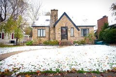 Stone Bungalow. Small stone bungalow style Northern American home with snow on the lawn. The style of architecture is similar to that found in Europe Royalty Free Stock Image