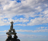 Stone Cairn 1. A stone cairn placed against a big blue sky with puffy white clouds to contrast royalty free stock photo
