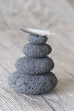 Stone cairn. Stacked pebble with feather on wooden background stock photo
