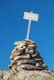 Stone cairn with empty white wooden label Stock Photography