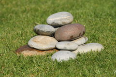 A stone cairn in the grass. In the garden Royalty Free Stock Photo