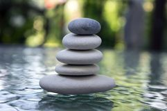 Stone cairn on green blurry background stock images