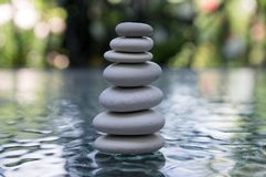 Stone cairn on green blurry background, light pebbles and stones Royalty Free Stock Photos