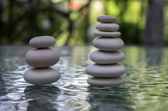 Stone cairn on green blurry background, light pebbles and stones stock photos