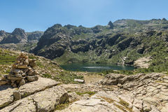 Stone cairn overlooking Lac de Melo in mountains of Corsica Royalty Free Stock Images