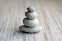 Stone cairn on striped grey white background, four stones tower, simple poise stones, simplicity harmony and balance, rock zen stock photos