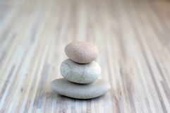 Stone cairn on striped grey white background, three stones tower, simple poise stones, simplicity harmony and balance, rock zen. Sculptures royalty free stock photos