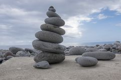 Stone cairn tower, poise stones, rock zen sculpture, light grey pebbles. Atlantic ocean coast, stone cairn tower, poise stones, rock zen sculpture, light grey royalty free stock photography