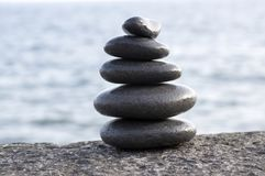 Stone cairn tower, poise stones. Rock zen sculpture, light grey pebbles, black volcanic pebbles royalty free stock images