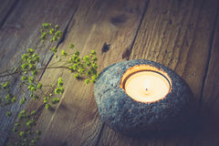 Stone candle holder with tea light on aged wood background, delicate yellow flowers Royalty Free Stock Photography