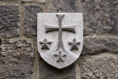 Stone Carmelite Order coat of arms. With a cross and three stars on old stone wall Royalty Free Stock Images