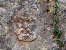 Stone carved face, embedded in wall. Royalty Free Stock Image