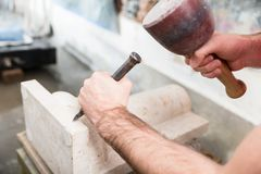 Stonemason working at marble pillar. Stone carver working with hammer and chisel at marble column Royalty Free Stock Photography