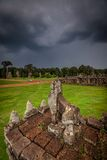 Stone carving of Angkor ruin with stormy sky Stock Images