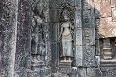 Stone carving at Angkor Wat Cambodia. Stone deity symbols carved into the rocks at the Angkor Wat historic complex. Many temple walls have Buddhist and Hindu stock images