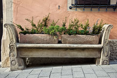 Stone carving bench in old town. Ancient stone bench with flower beds stands against a wall in old town Royalty Free Stock Photo