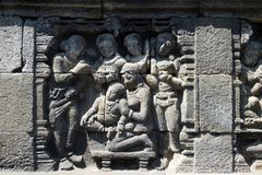 Stone carving. at Borobudur temple, Magelang, Indonesia. Closeup wall ornamented with bas-reliefs religion scene. Highly detailed stone carving. Borobudur royalty free stock photo
