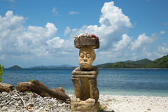 Stone carving man sitting on the beach on high travelling season of Indonesia. Royalty Free Stock Image
