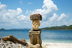 Stone carving man sitting on the beach on high travelling season of Indonesia. Royalty Free Stock Photo