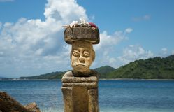 Stone carving man sitting on the beach on hight season Indonesia. Stock Images