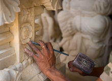 Stone carving at process. Stone mason at work carving an ornamental relief Royalty Free Stock Image