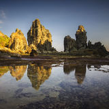 Stone castle at hidden beach of Lombok woith blue sky and long exposure water Stock Photo
