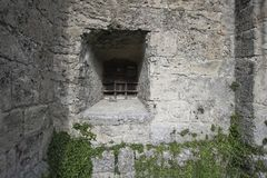 Ancient castle in Bavaria in Germany. Stone castle walls in Titmoning in Bavaria doorway old window with iron bars XII-XIII century Royalty Free Stock Photo