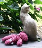 Stone cat with soaked pink teddy bear on porch stock photo