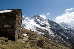 Stone chalet in Alps. Scenic view of stone chalet on snowy alpine mountains with blue sky background Stock Image