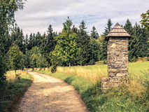 Stone chapel on pathway in summer countryside. Stone chapel or shrine next to the beaten track, relaxed walk, summer countryside landscape, bottom copy space Royalty Free Stock Photo
