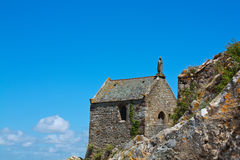 Stone chapel with a saint on the roof Stock Images