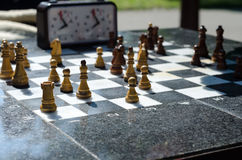 Stone chessboard with wooden chess on it Stock Photo