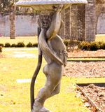 Stone Child Statue Holds Bird Bath at Historic Gardens Open to the Public royalty free stock photos