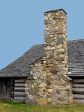 Stone chimney on a log cabin. Stock Images