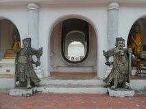 Stone Chinese warrior sculptures guarding the entrance  door on corridor around Phra Pathomchedi Pagoda Stock Photos