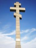 Stone Christian cross. Tall stone Christian cross monument Christ against a sunny cloudy blue sky Stock Photo