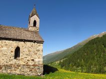 Stone church Alpine mountain valley spring summer. A simple stone church occupies a tranquil spot in a green Alpine valley carpeted by dandelions, beneath a Royalty Free Stock Photos